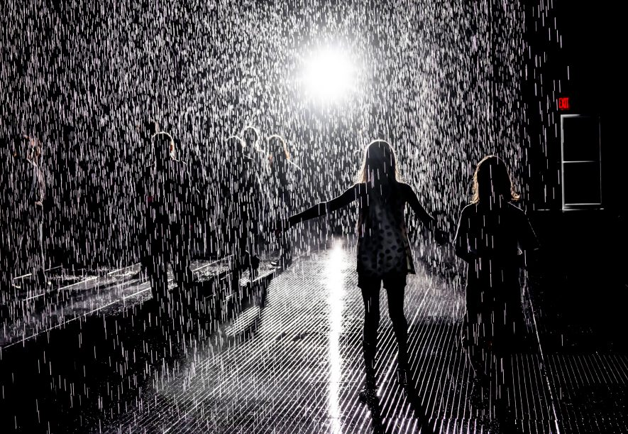 Rain Room exhibit at MOMA, by Random International.  The exhibit is in a lot next to MOMA, in a large space of falling rain that senses and parts for the people under it.